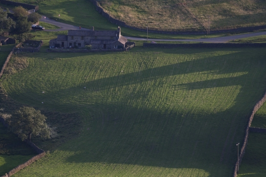 A farmhouse in Reeth in the Yorkshire Dales is seen amongst late evening shadows